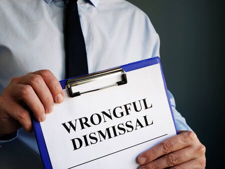 Man holds papers about Wrongful dismissal. Standard-Bild