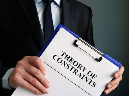 Businessman holds toc theory of constraints papers. Banco de Imagens