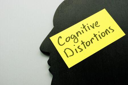 Distorsiones cognitivas firman en la forma de la cabeza como símbolo de la mente.