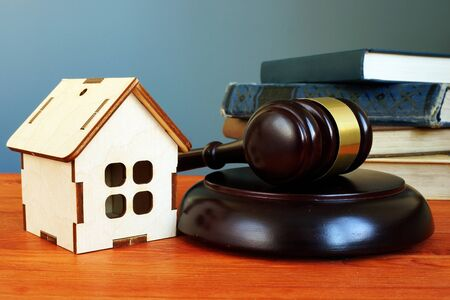 Property law concept. Gavel and tiny home on the desk.