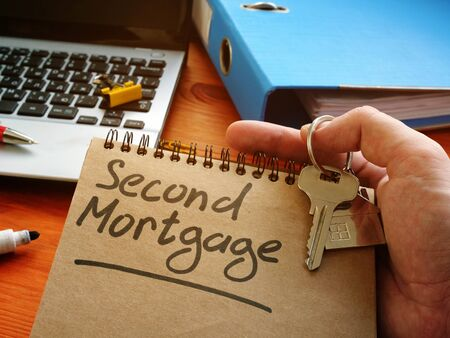 Hand holds sign second mortgage and key.