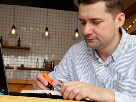 Man is underlined and working with laptop in the cafe.