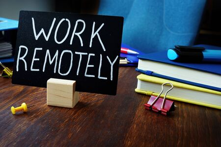 Work remotely sign on the desk about remote job. Imagens