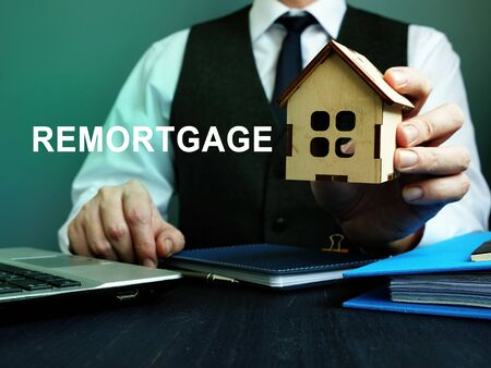 Man holds wooden home and sign remortgage.