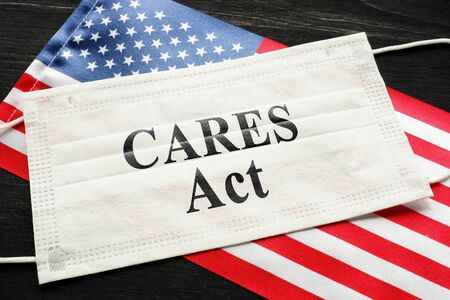 American flag and mask with sign cares act. Coronavirus Aid, Relief, and Economic Security law concept. Standard-Bild