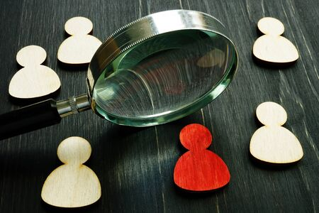 Talent acquisition. Magnifying glass and wooden figures as symbol an employee.