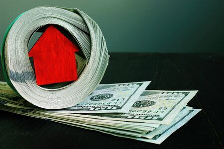 Dollars and small red home. Property invest concept. Foto de archivo