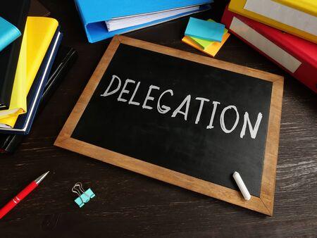 Delegation written in chalk on a blackboard. Delegating concept.
