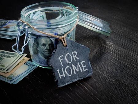 Savings for buying property. Jar and money with label for home.