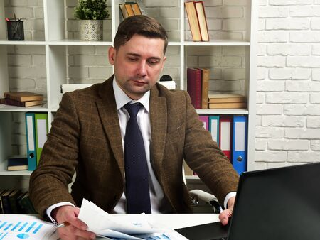 Businessman in a suit works with documents in the office. The workplace of the manager.