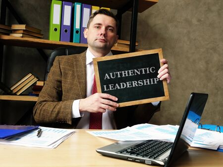 Authentic Leadership concept. Young businessman holds a black board.