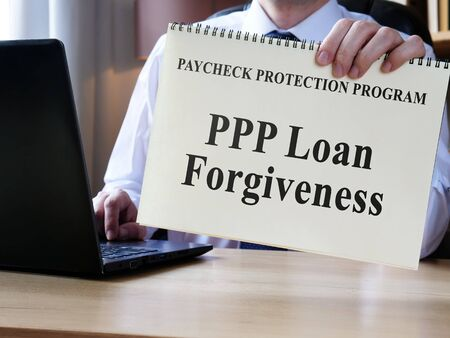 Accountant shows form for PPP loan forgiveness. 版權商用圖片