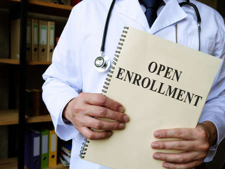 Doctor shows Annual open enrollment stack of papers.