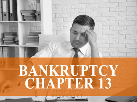 Bankruptcy chapter 13 concept. A pensive businessman is sitting at the table.