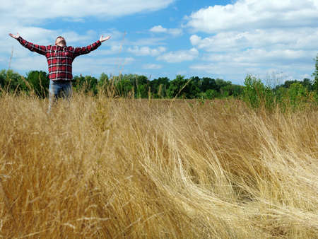 Joyful young man stretches out his hands to the sky while standing in a field in nature. Joy and relaxation. Imagens