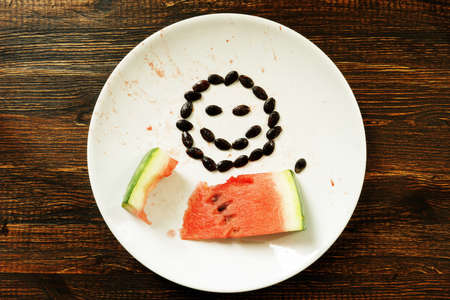 Vegetarian fruit diet. A slice of watermelon and a smile on a plate.
