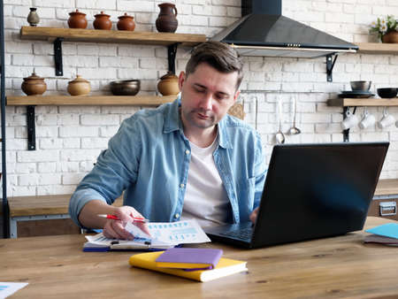 A man works at home with documents and a laptop. Remote work.