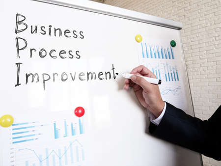 Business Process Improvement BPI manager writes on a whiteboard. Imagens
