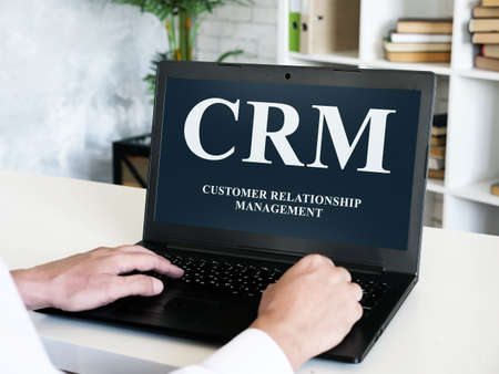 Customer relationship management CRM inscription on the laptop screen. Imagens