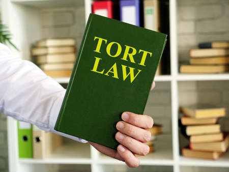 Hand shows a Tort law book in the office.
