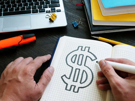 Hands are drawing a dollar sign in a notebook. Personal finance and wealth management. Imagens