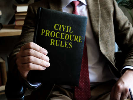 Civil Procedure Rules. Businessman holds a book in his hands.