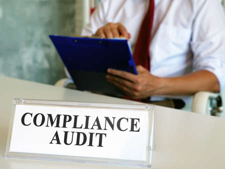 Compliance audit concept. The auditor checks the papers.