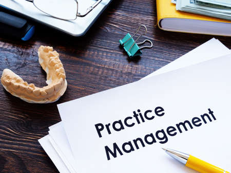 Dental practice management guidelines on the desk.