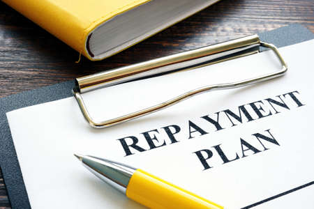 Repayment plan with clipboard and yellow pen.