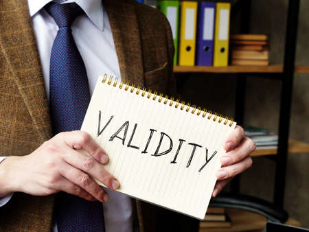 Validity concept. A man in a suit holds a handwritten lettering.
