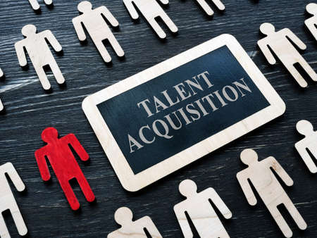 Talent acquisition concept. Small plaque and wooden figures.