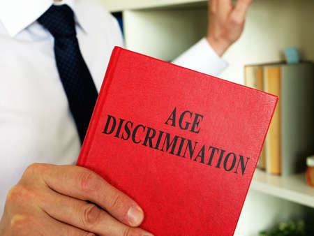 A lawyer shows an Age discrimination law book in the office. Imagens