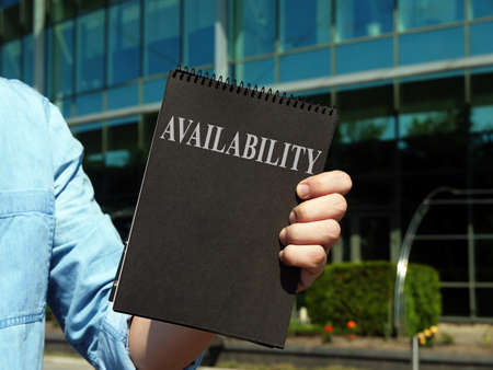 Availability. A man holding a notebook with the inscription.
