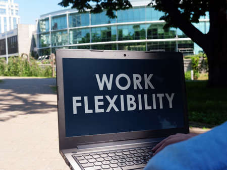 Work flexibility. A man in the park reads information on a laptop. Imagens