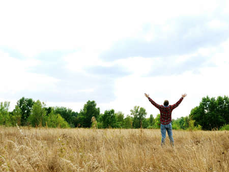 A man in an autumn field stretches out his hands to the sky. Imagens