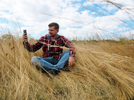 A man in the autumn nature takes a selfie and uses a smartphone.