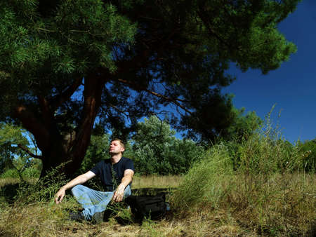 Male tourist meditates while sitting under a tree in the forest.