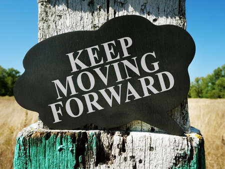 Keep moving forward motivational quote. Old milestone on the field. Stockfoto