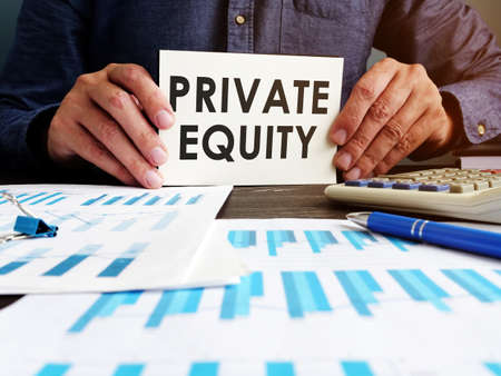 Private equity concept. Manager sitting at the table holds an inscription.
