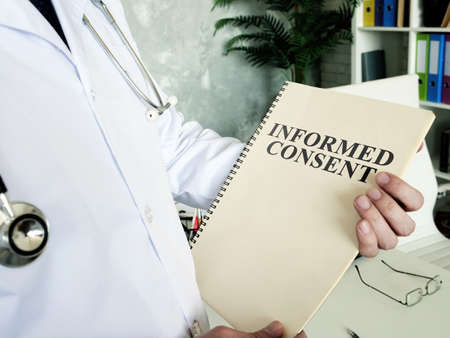 Doctor shows documents and informed consent form. Reklamní fotografie