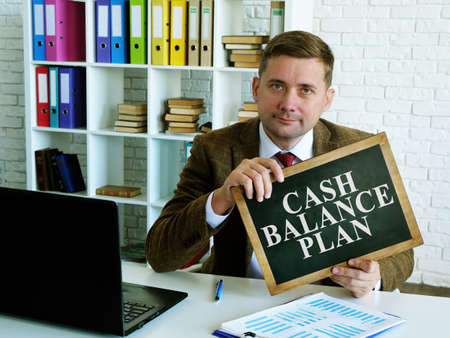 Cash balance plan. A man holds a sign with the inscription. Imagens