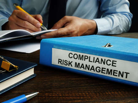 Compliance risk management papers in the blue folder.