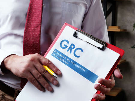 Businessman with GRC Governance risk management and compliance documents.