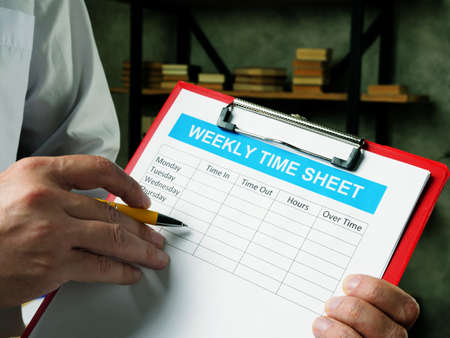 The manager fills out the weekly time sheet for employees. Reklamní fotografie