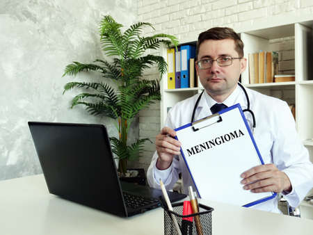 Meningioma concept. The doctor holds a diagnosis in his hands.