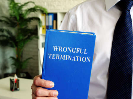 Wrongful termination. The employee holds a book in his hands.