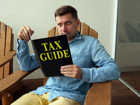 Tax guide concept. A guy sitting in a chair reads a book. Reklamní fotografie