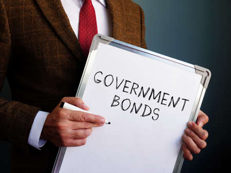 Government bonds. A financial advisor is holding a board with the inscription.