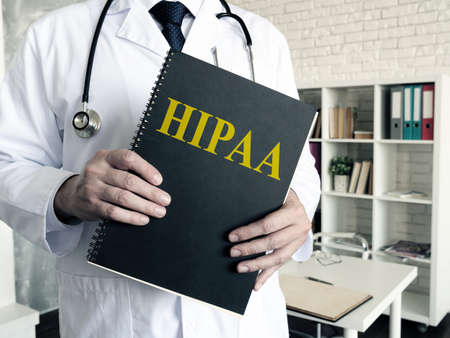 Doctor holds papers about HIPAA certification. Health Insurance Portability and Accountability Act. Reklamní fotografie