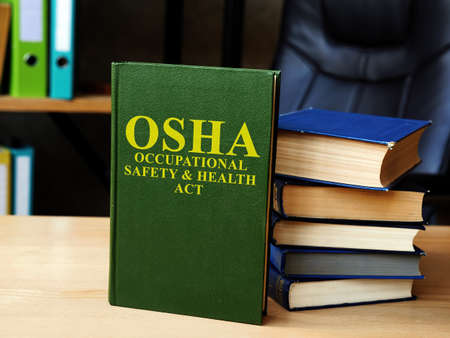 Occupational Safety and Health Act OSHA book and stack of documents. Reklamní fotografie